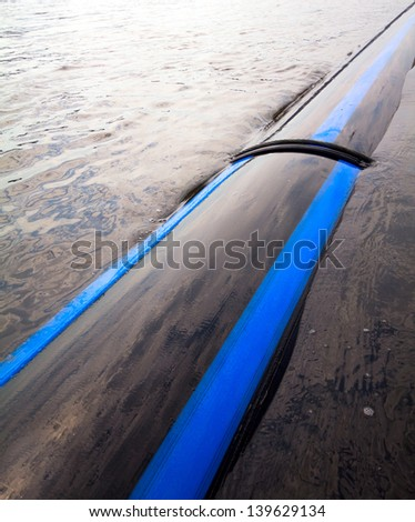 pipe laid in the river along the coast - stock photo