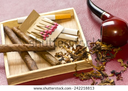 Pipe, tobacco, cigarettes, cigars, smoking, etc. on red leather background