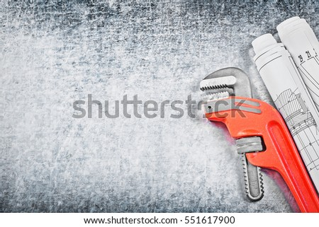 Pipe wrench and blueprints on metallic background copy space construction concept.