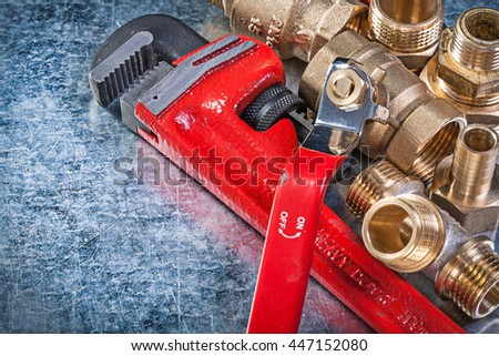 Pipe wrench brass nipple hose connectors lever ball valve on metallic background plumbing concept.