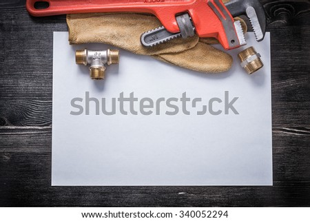 Pipe wrench copper plumbing fittings leather protective gloves white paper. - stock photo