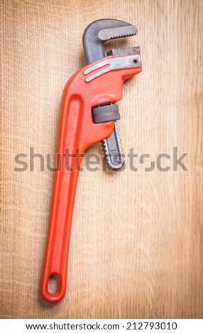 pipe wrench on wooden board - stock photo