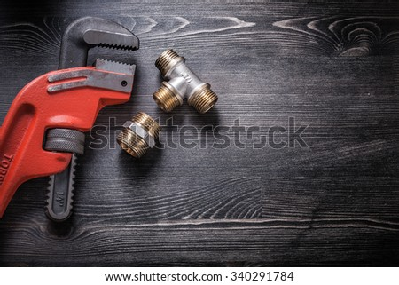 Pipe wrench plumbing fittings on wooden board. - stock photo