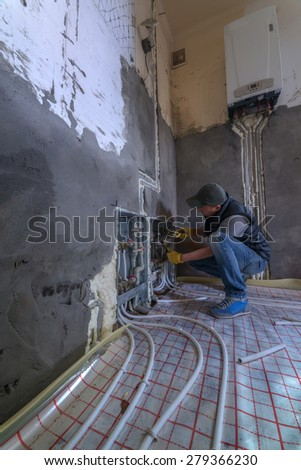 pipefitter installing system of heating - stock photo