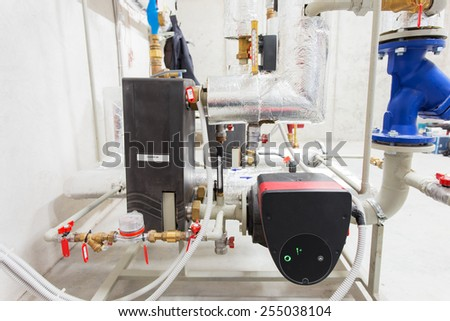 Pipeline installation and water pump in boiler room - stock photo