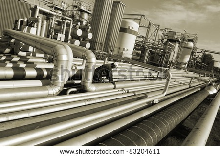 pipelines inside oil refinery, worker climbing on pipes, brown toning idea
