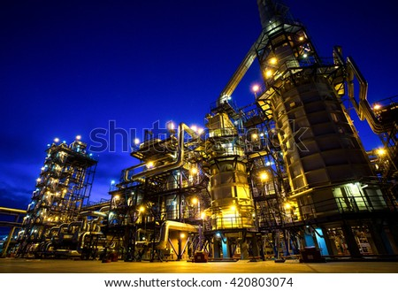 Pipes and buildings at big modern factory with lights - stock photo