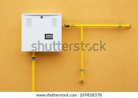 Pipes and gas-meter on orange wall - stock photo
