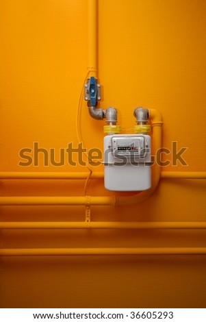 Pipes and gas meter on orange wall - stock photo