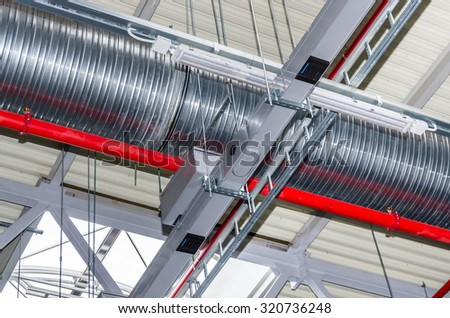 Pipes and other engineering services in industrial building - stock photo
