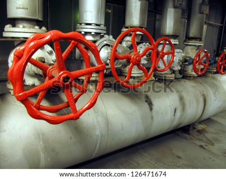 Pipes and valves with red knobs for hot water