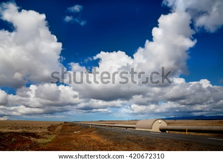 Pipes from heating plant along the road in Iceland - stock photo