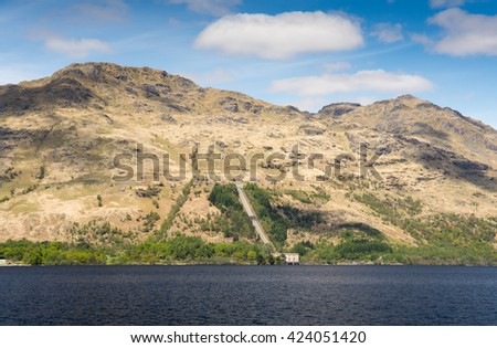 Pipes lead down a mountainside to Inveruglas Hydroelectric Power Station on the shores of Loch Lomond in the West Highlands of Scotland. - stock photo