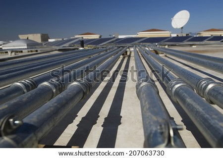Pipes leading to solar panels at solar power plant - stock photo