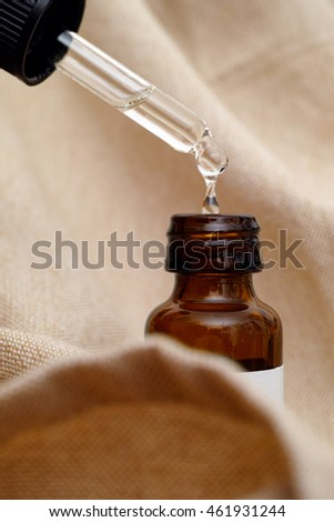 Pipette with drop of essential oil and bottle on beige textile.