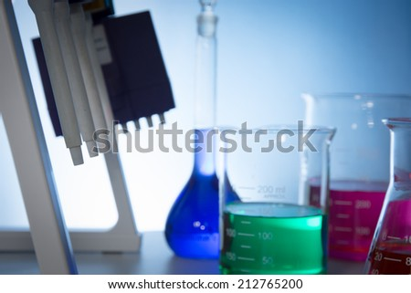pipettor, liquid-moving and glassware with color water in desk - stock photo