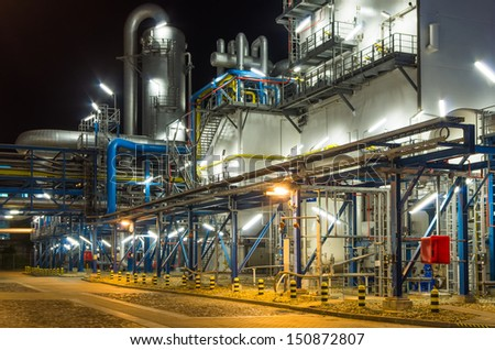 piping system inside of industrial plant at night