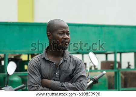 PIRA, BENIN - JAN 12, 2017: Unidentified Beninese man in grey shirt looks away and crosses his hands. Benin people suffer of poverty due to the bad economy.