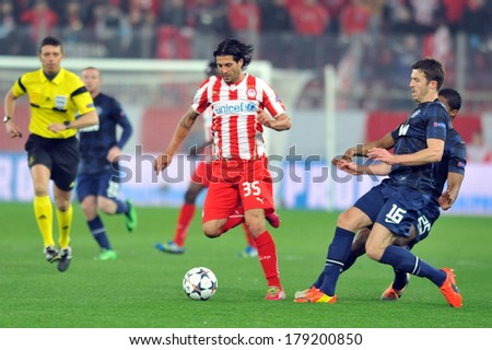 PIRAEUS, GREECE -FEB. 25. Olympiakos' Alejandro Dominguez, takes the ball from Manchester United's Michael Carrick,  during their Champions League soccer match, in Piraeus Feb. 25, 2014 - stock photo