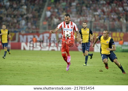 Piraeus,Greece Sept 16, 2014. Olympiacos Kostas Mitroglouwith the ball and Athletico's Miranda during the Champions League soccer match between Olympiakos and Atletico at Karaiskakis Stadium  - stock photo
