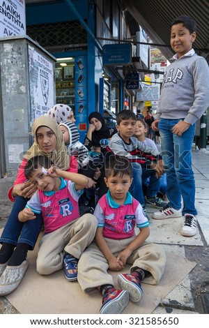 PIRAEUS, GREECE: SEPTEMBER 19, 2015: Family of immigrants and refugees from Middle East and North Africa sitting at the cardboard box at street. - stock photo