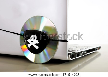 Pirate Eye patch on cd or dvd disk and computer representing piracy, illegal download and copyright violation - stock photo