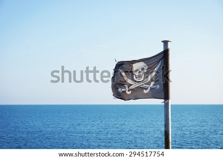 Pirate flag fluttering in the sea breeze - stock photo