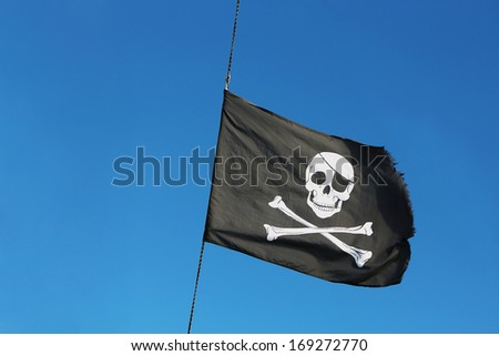 Pirate flag on the sky - stock photo