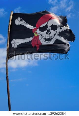 Pirate flag waving over blue sky - stock photo