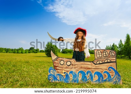Pirate girl with black hat, sword stands on ship - stock photo
