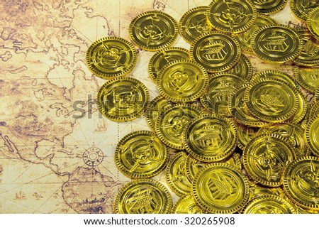 pirate golden coin on a old world map - stock photo