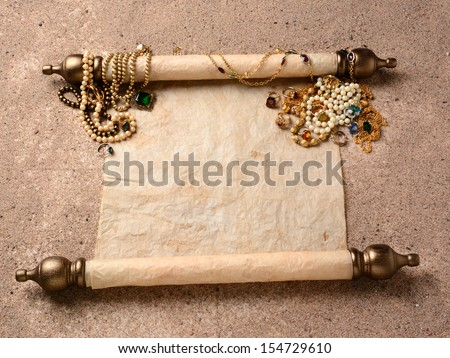 Pirates Booty. An ancient scroll laying on beach sand with jewelry scattered on it upper end. The scroll is blank ready for your treasure map or copy. - stock photo