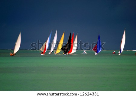 Pirogues on the horizon in front of dark clouds (Mauritius) - stock photo