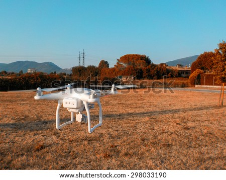 PISA, ITALY - JULY 19, 2015: Drone Phantom 3 hovers in the air. DJI Phantom 3 is the latest drone from market leader DJI. - stock photo