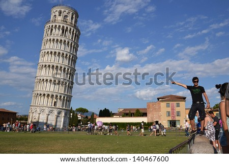 PISA, ITALY - JULY 16: Tourists posing in front of the Leaning tower of Pisa on July 16 2012 in Pisa, Italy. - stock photo