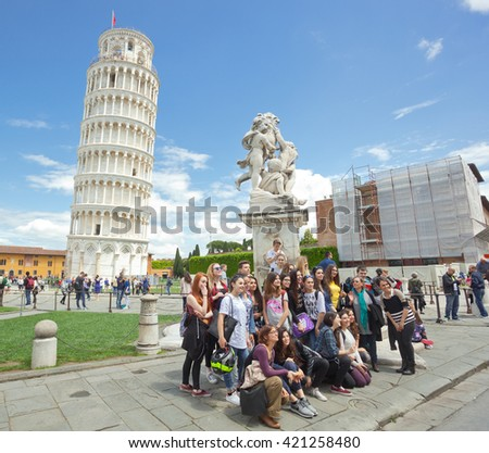 Pisa, Italy - 14 May 2016: Group of students on educational trip Cathedral Square of Pisa, Italy. The tower is a well known landmark worldwide for its unintended tilt.