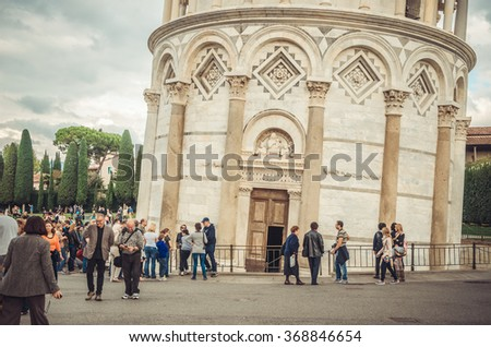 Pisa, Italy - October 19, 2013: Tourists by the entrance to the world famous miracle Leaning Tower of Pisa. The construction of this beautiful bell tower started in 1173 and its architect is unknown.