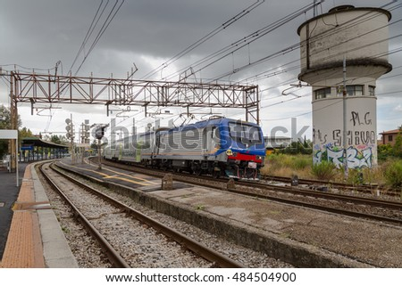 PISA, ITALY - SEPTEMBER, 17 2016: Trenitalia Regional Passenger Vivalto train with Electric Locomotive Model E464 is departing from the Station of Pisa San Rossore.