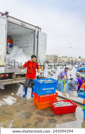 PISCO, PERU, MAY 21, 2014: Man loads boxes of freshly caught fish into a refrigerated truck in fishermen's wharf of San Andres.  - stock photo