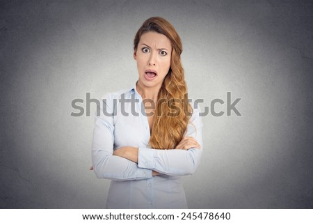 Pissed of angry young woman with disgusted face expression shouting on grey wall background  - stock photo