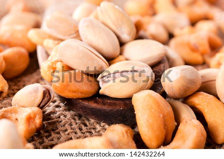 Pistachio and cashew nuts on wooden spoon. Selective focus in the middle - stock photo