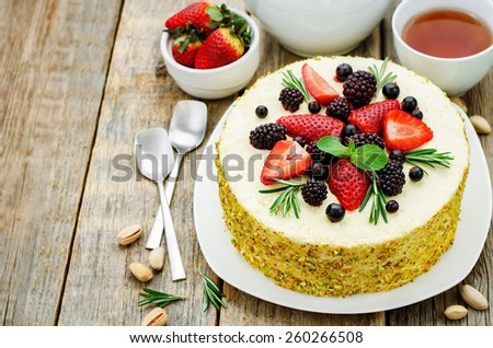 pistachio cake with berry compote and rosemary mousse on a dark wood background. tinting. selective focus - stock photo