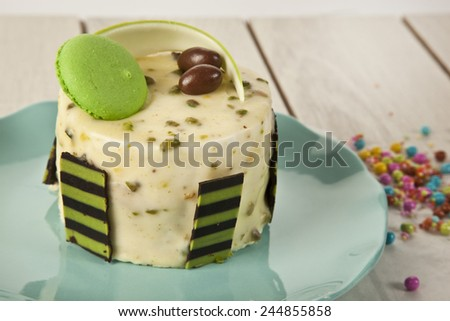 Pistachio cheesecake, mousse cake with chocolate decoration on a white plate - stock photo