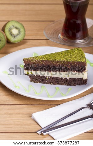 Pistachio cheesecake, mousse cake with nuts and hot drink decoration on a wooden table