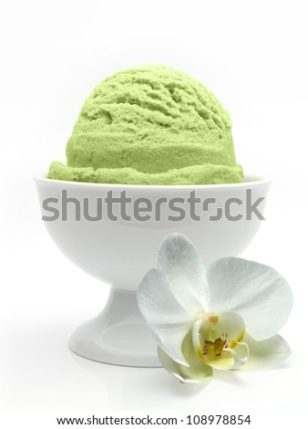 Pistachio ice cream in bowl with orchid on white background - stock photo