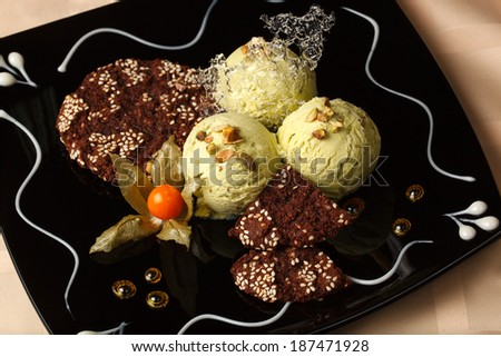 Pistachio ice cream topped with roasted nuts and served with chocolate cookies garnished with a ripe cape gooseberry on a beautifully decorated plate - stock photo