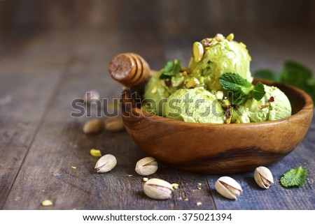 Pistachio ice cream with chopped nuts and honey on a rustic background. - stock photo