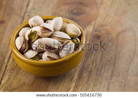 Pistachio nut in bowl on wood table - stock photo