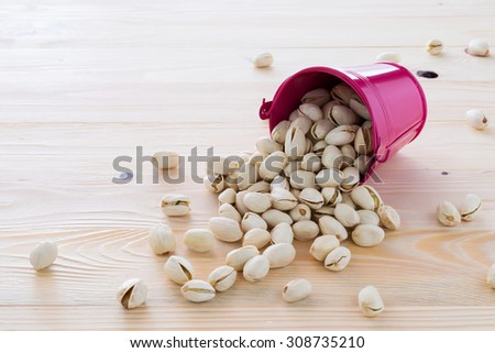 Pistachio nuts are lined on the wooden floor. - stock photo