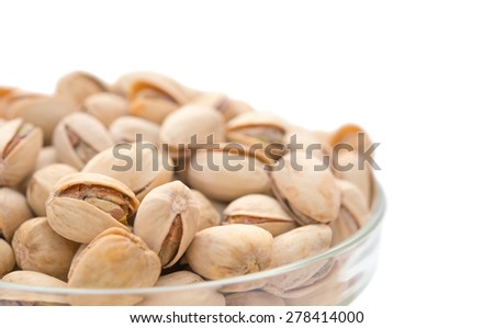 Pistachio nuts in a glass bowl close up with clipping path - stock photo